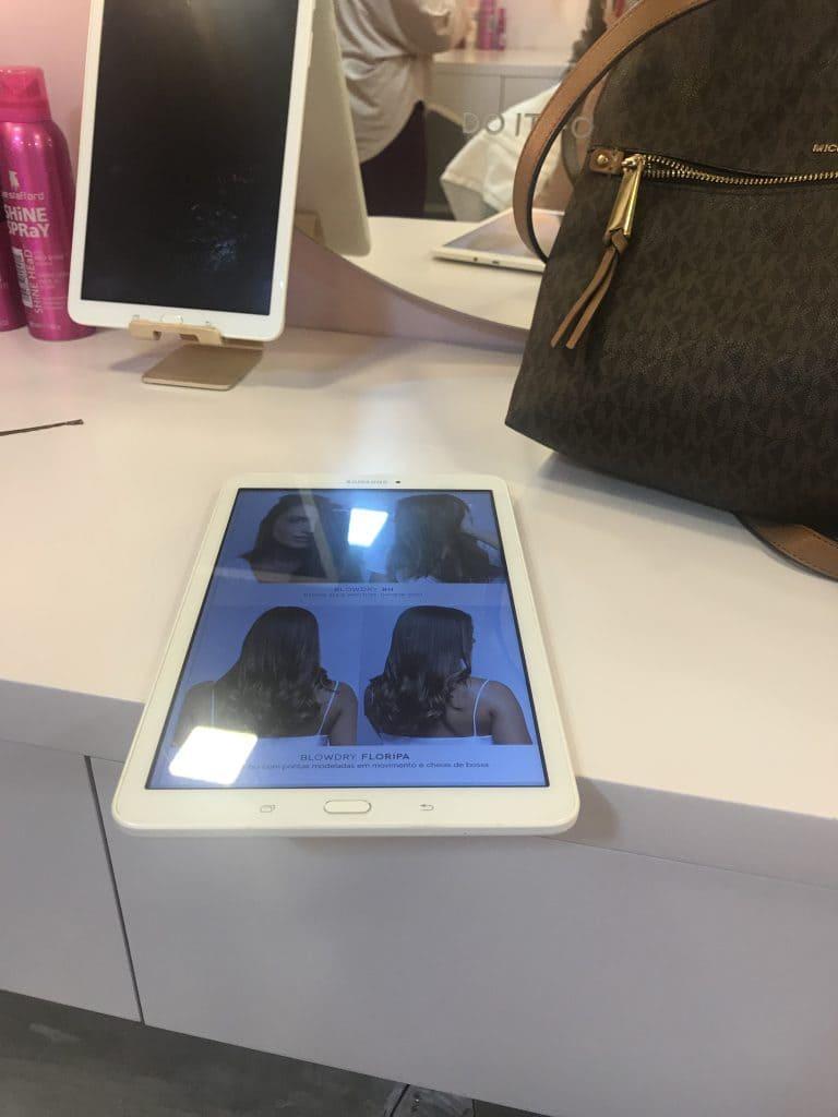 Tablet com cardápio de maquiagens e blow-dries disponíveis no 55 Beauty Bar.