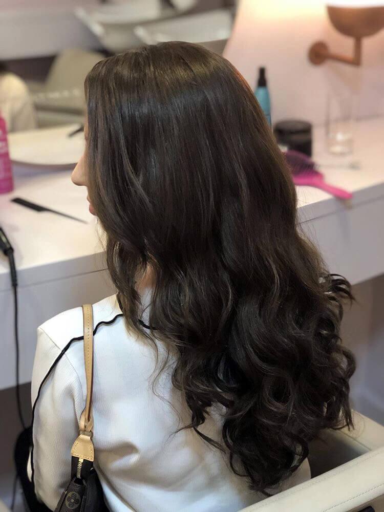 A blogueira Daniela Maksoud está de costas, usa bolsa Pochette Accessoires da Louis Vuitton, veste camisa branca com detalhes em costura preta e tem os cabelos castanhos estilizados com babyliss em ondas largas no estilo da modelo Gisele Bündchen.
