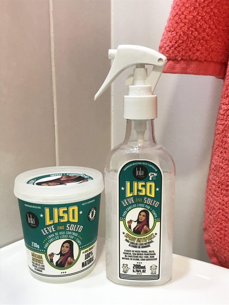 Máscara e spray antifrizz da linha Liso, Leve and Solto da Lola Cosmetics em cima da pia de um banheiro com uma toalha ao fundo.