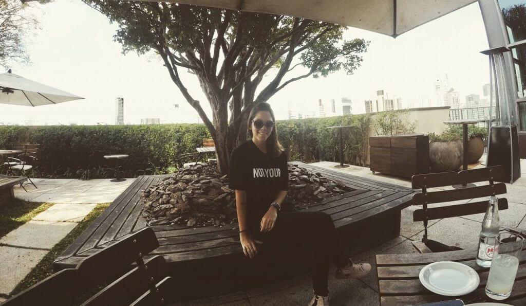 Manuela Brasão veste blusa preta, legging preta e óculos de sol sentada em um banco de madeira no shopping Cidade Jardim em São Paulo.