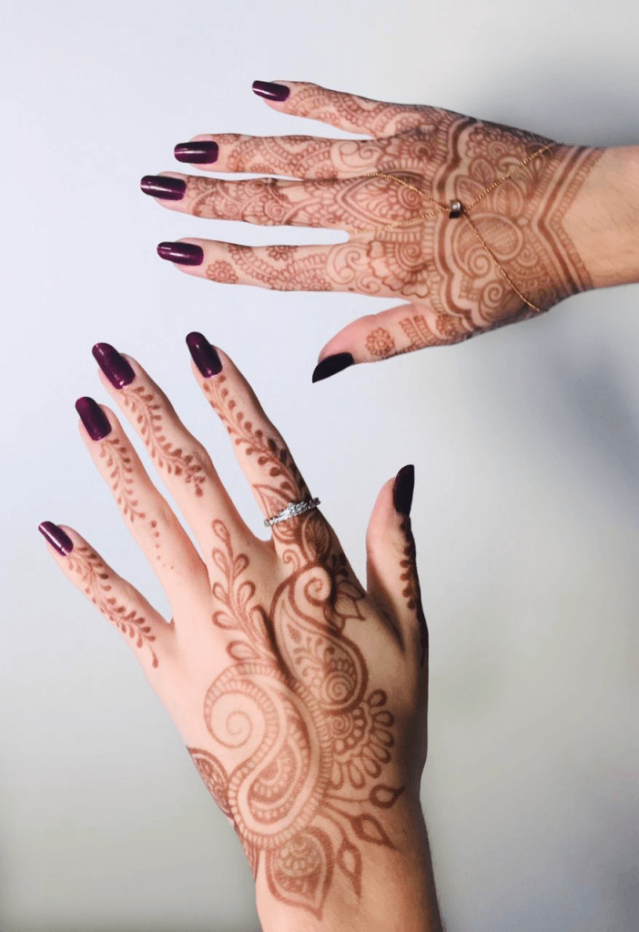 Mãos com tatuagem de henna ou mehandi.
