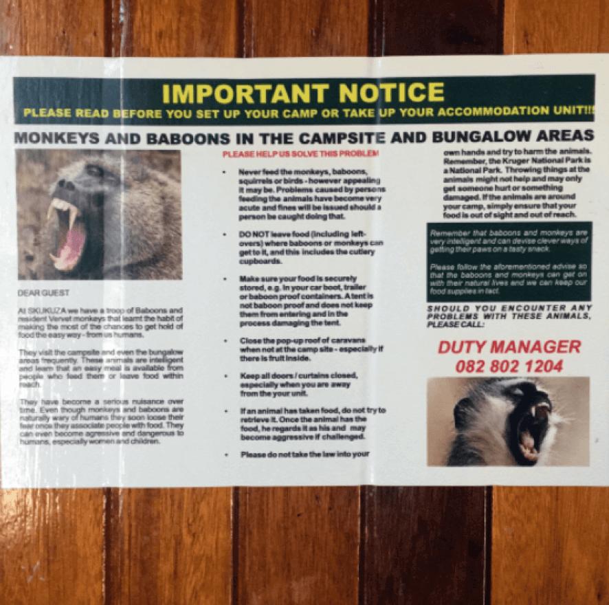 Placa com aviso sobre a presença de babuínos nos acampamentos do Kruger National Park.