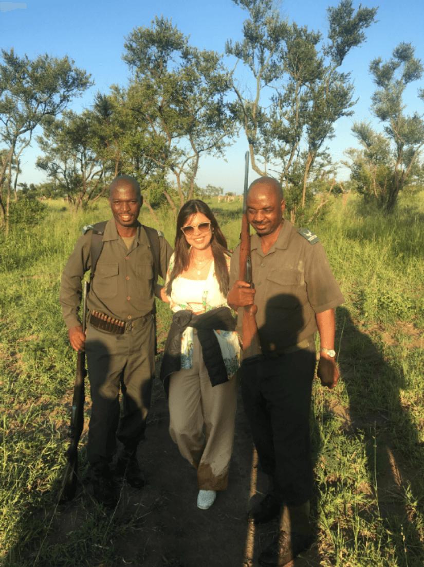 Ana Paula Kasznar posa para foto com zebras no fundo e dois rangers do safári no Kruger National Park.