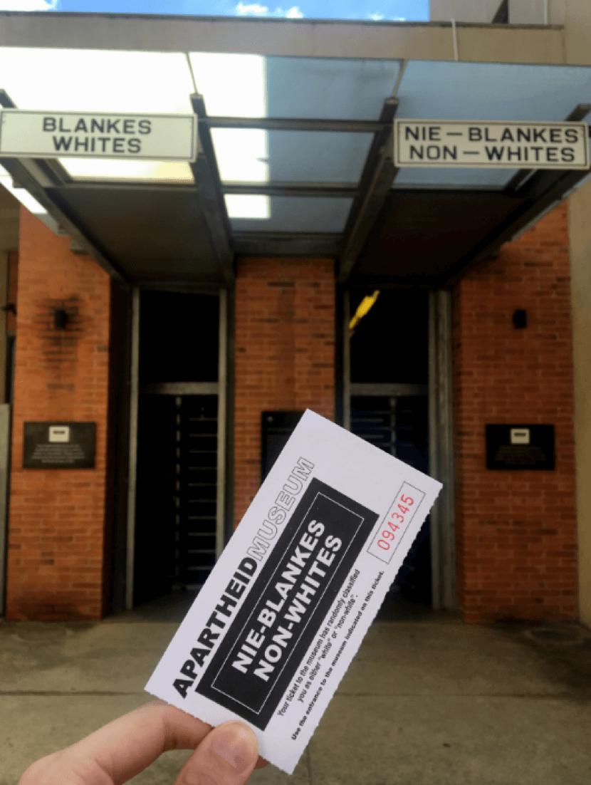 Mão segura ingresso do Apartheid Museum em frente às duas portas do museu, uma para brancos e outra para negros.