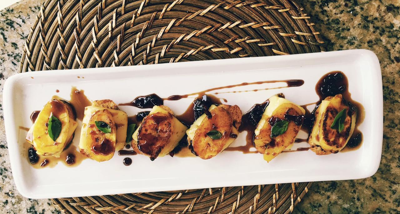 Prato com torradinhas cobertas com queijo manteiga, banana da terra e geléia suave de pimenta.