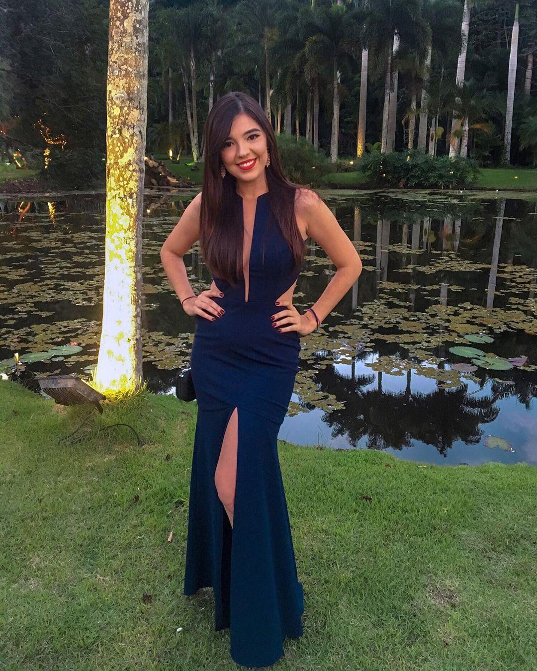 Ana Paula Perrone Kazsnar posa para foto com vestido longo azul marinho com fenda, decote em V profundo e tule ilusion.