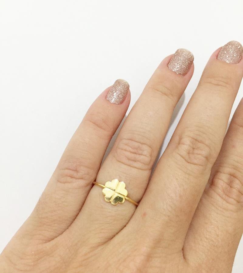 Mão com unhas com esmalte de glitter e anel de trevo dourado.