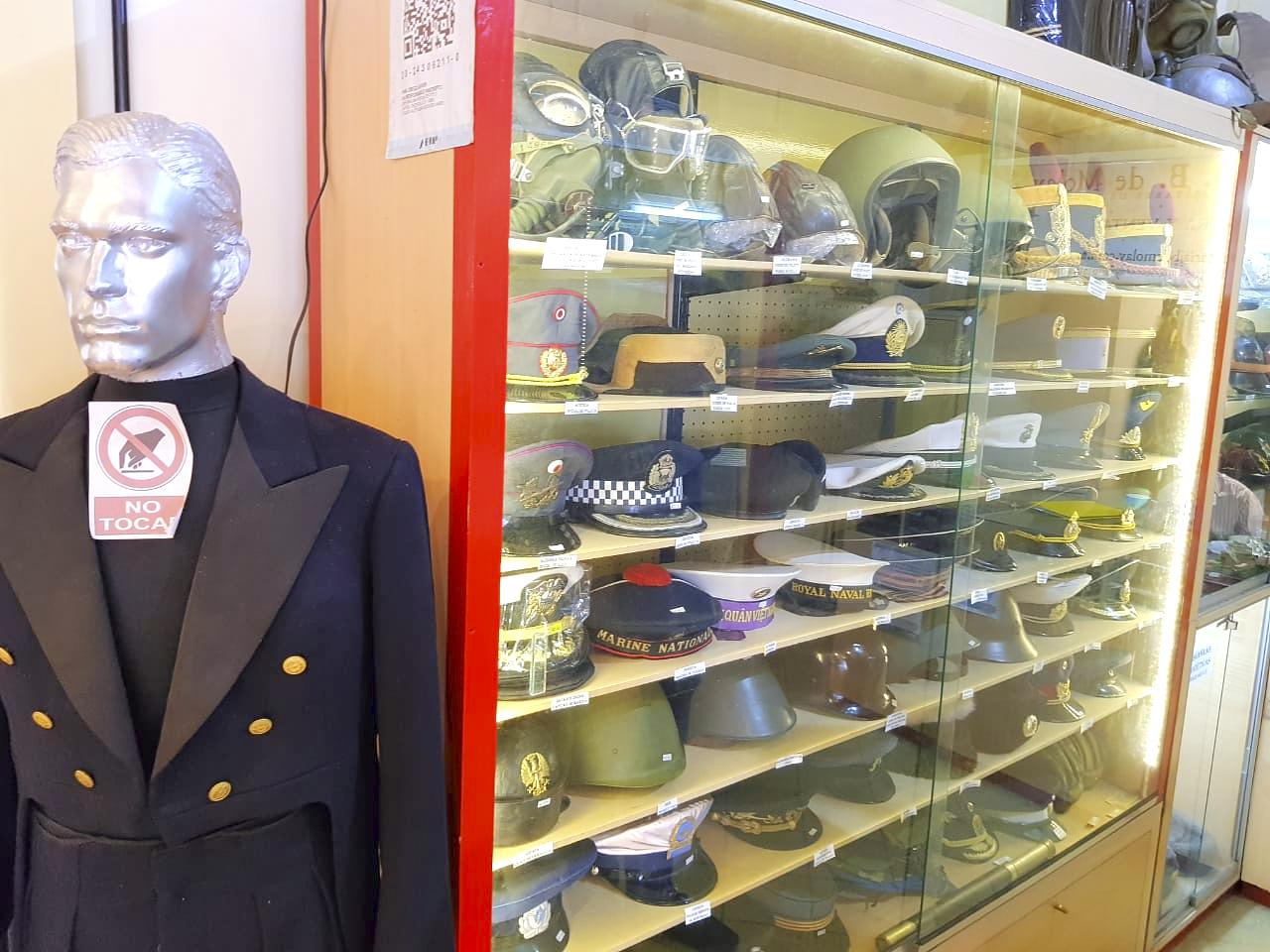 Capacetes militares antigos dentro de armário e manequim com uniforme militar em lojinha na feira de San Telmo.