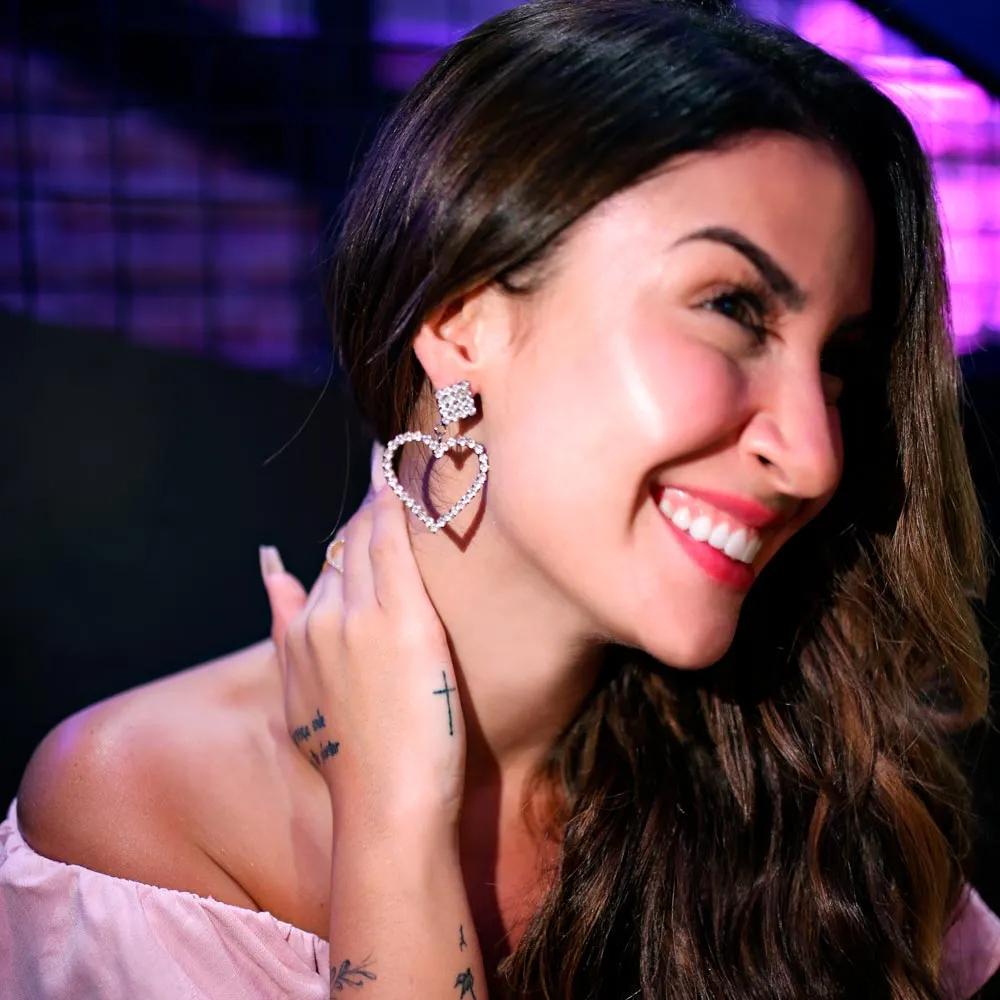 Bianca Andrade usa cabelo solto e lateralizado, blusa rosa bebê e brincos de coração de strass.