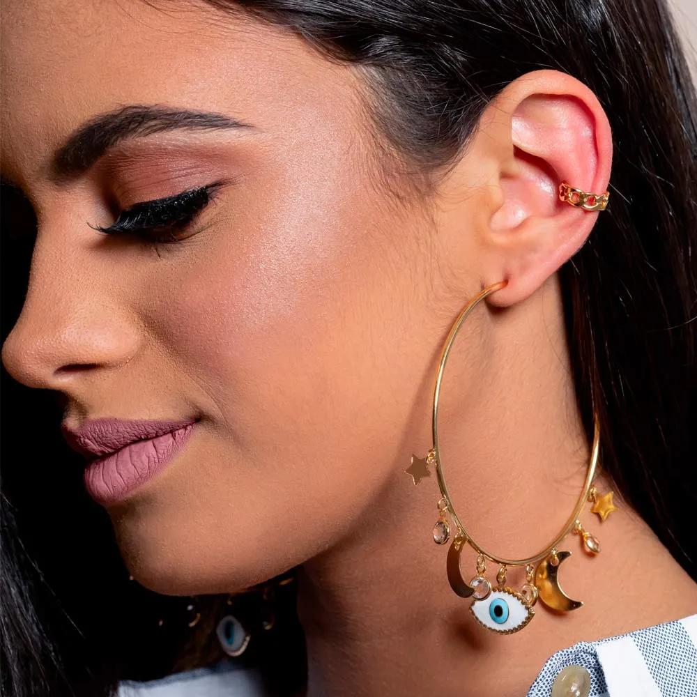 Modelo usa piercing falso dourado e brinco de argola dourada com pingente de olho turco.