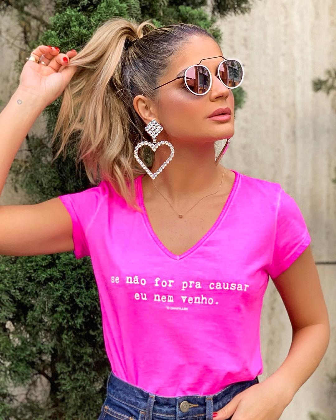 Thássia Naves usa cabelo preso em rabo de cavalo alto, camiseta rosa pink escrito se não for pra causar, eu nem venho, maxi brincos de coração com strass prata e óculos de sol.