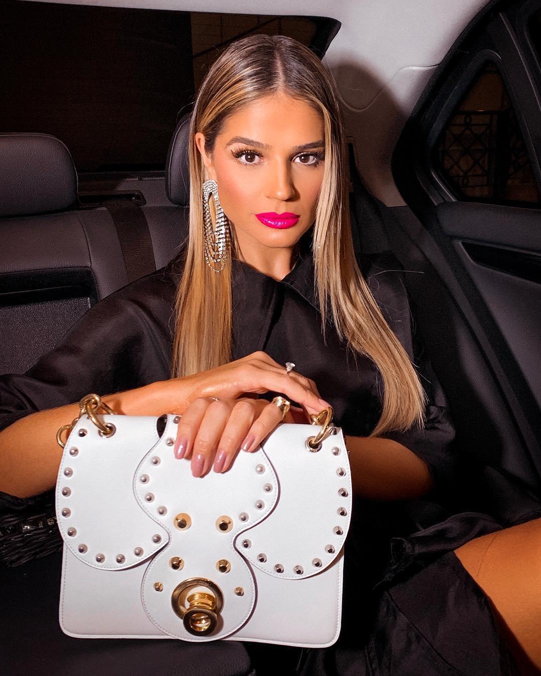 Thássia Naves usa cabelo solto, liso e repartido no meio, batom rosa pink, roupa preta, bolsa branca com detalhes em dourado, maxi brincos de franjas cravejadas de strass e anéis.