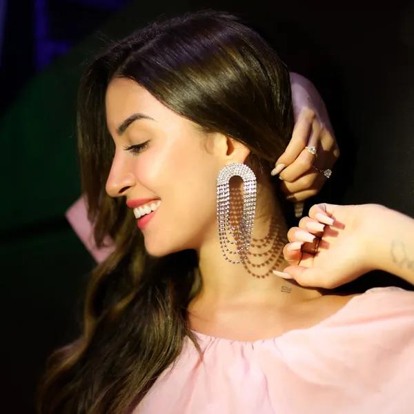 Bianca Andrade usa cabelo solto lateralizado, maxi brincos ovais cravejados de strass, blusa rosa bebê e anéis.