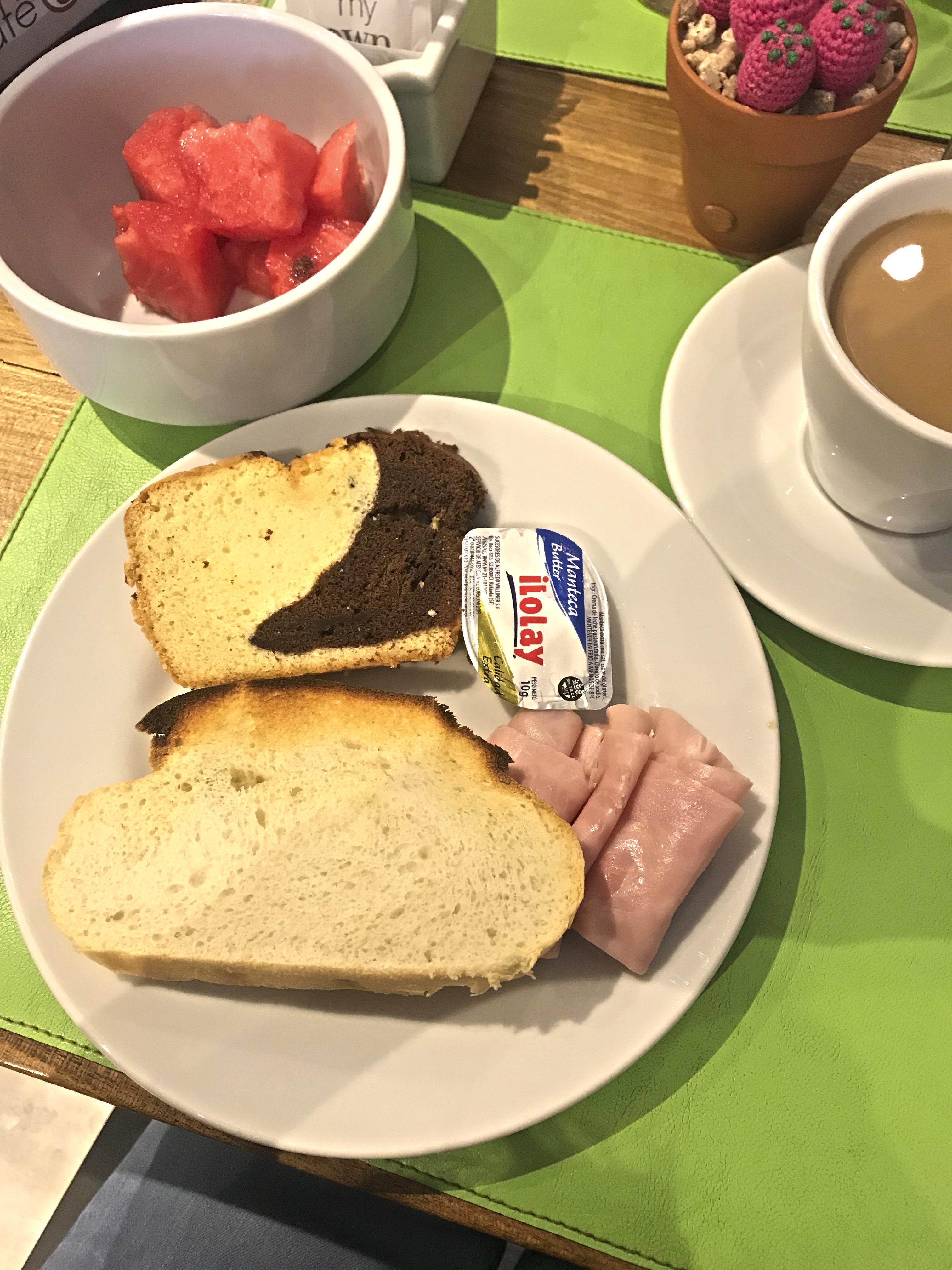 Pedaços de melancia em um pote, fatia de bolo de branco com chocolate, torrada, manteiga e presunto em um prato e xícara com chocolate quente.
