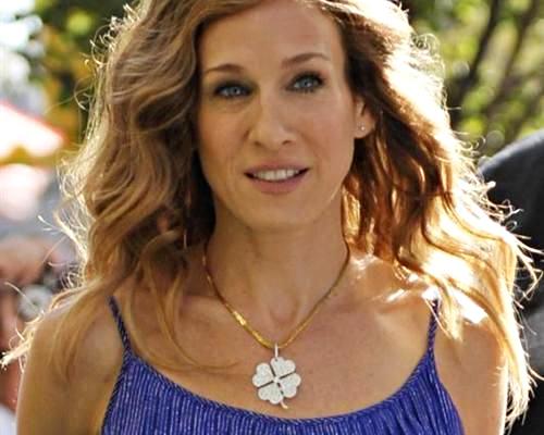 Mulher com colar de trevo e vestido azul.