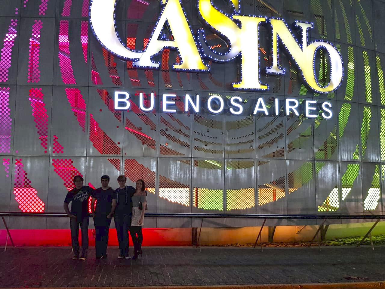 Família em frente a letreiro com luzes neon escrito Casino Buenos Aires.