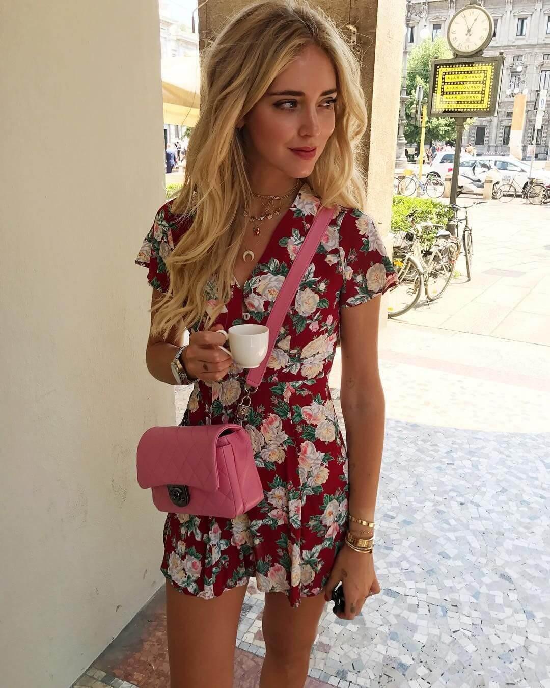 Blogueira loira com cabelos compridos usa vestido floral, bolsa Chanel rosa candy e colares e pulseiras dourados e segura xícara de café na mão.