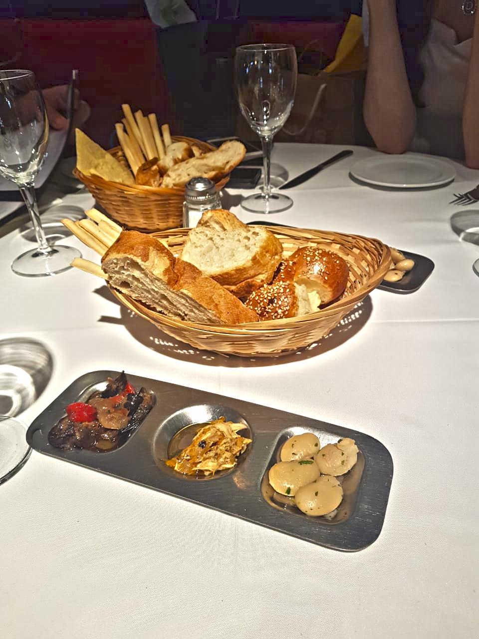 Cestinhas de pães em uma mesa com toalha branca.
