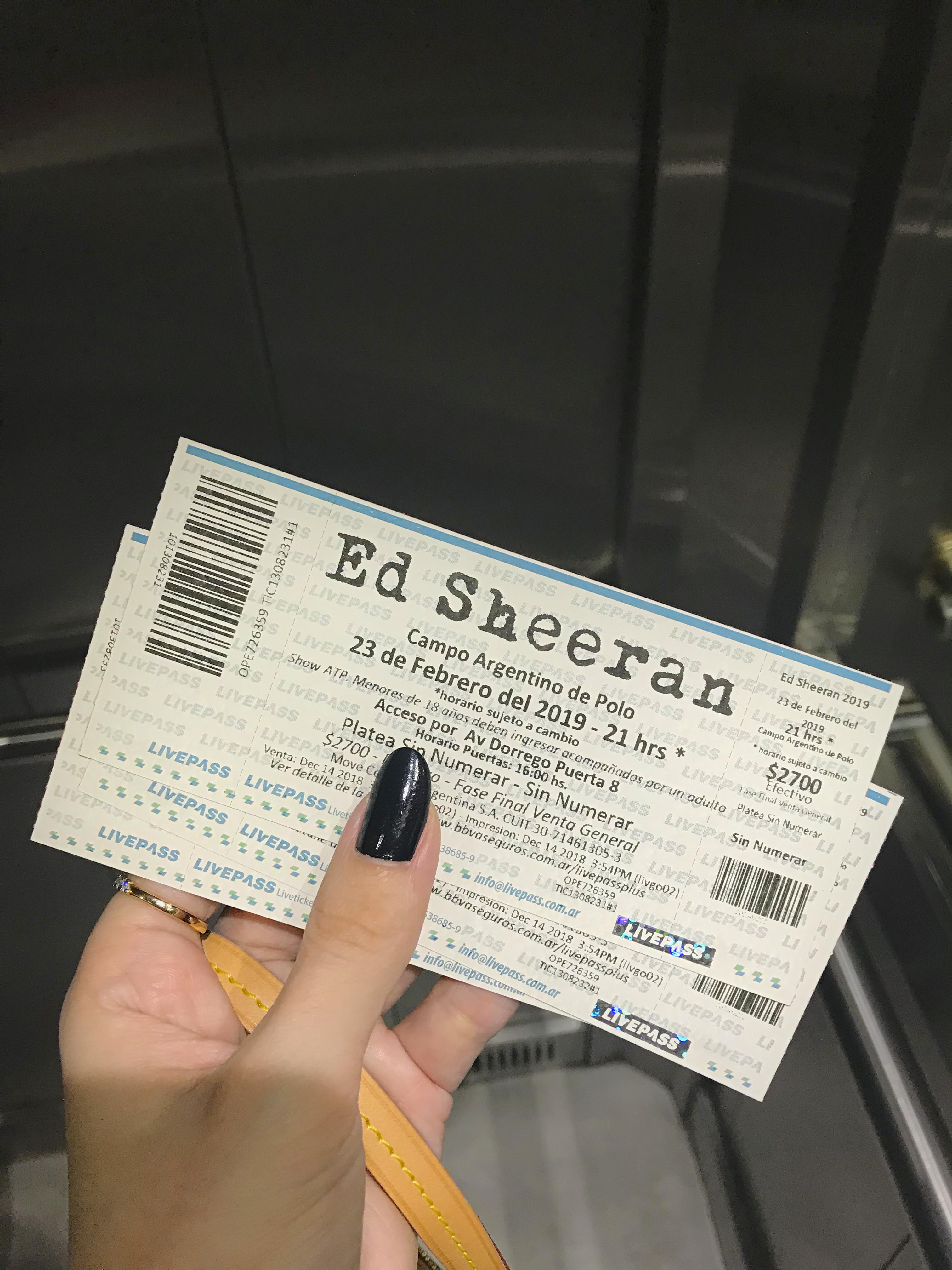 Mão com unhas pretas segurando bolsa e ingressos do show do Ed Sheeran dentro de um elevador.