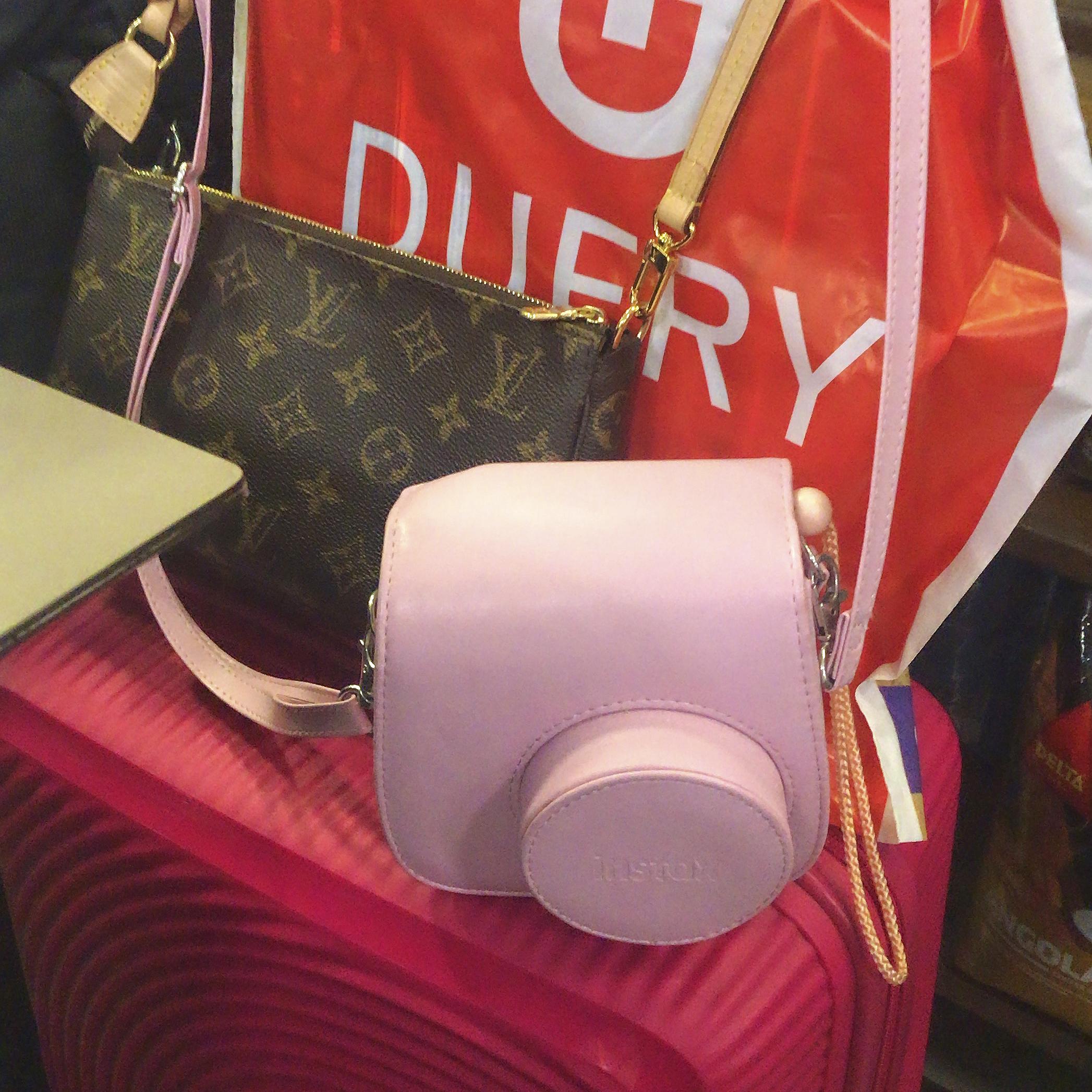 Mala de mão rosa pink da Samsonite, bolsa Pochette Accessoires da Louis Vuitton, câmera Polaroid Instax Mini rosa bebê e sacola vermelha do free shop Dufry.