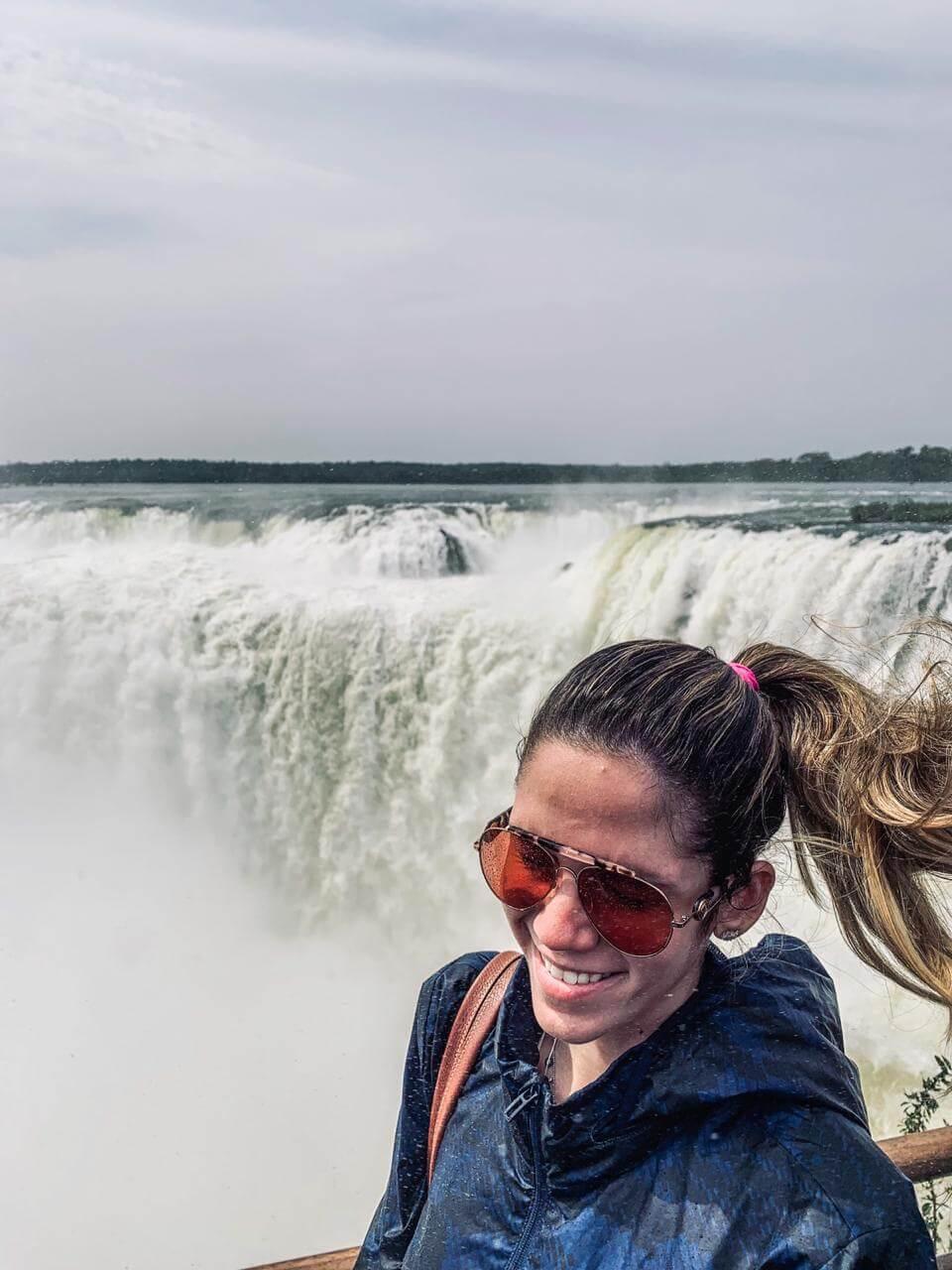 Manuela Brasão posa para foto sorridente com rabo de cavalo ao vento e cataratas de Foz do Iguaçu ao fundo.