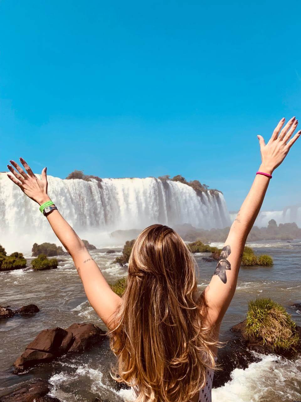 Manuela Brasão com os braços abertos para as cataratas de Foz do Iguaçu.