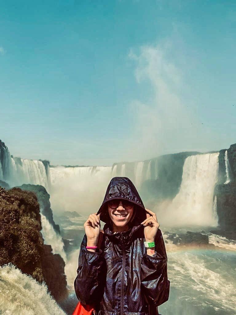 Manuela Brasão com capa de chuva nas cataratas de Foz do Iguaçu.
