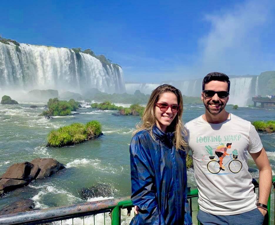 Manuela Brasão e Diego posam para foto com as cataratas de Foz do Iguaçu ao fundo.