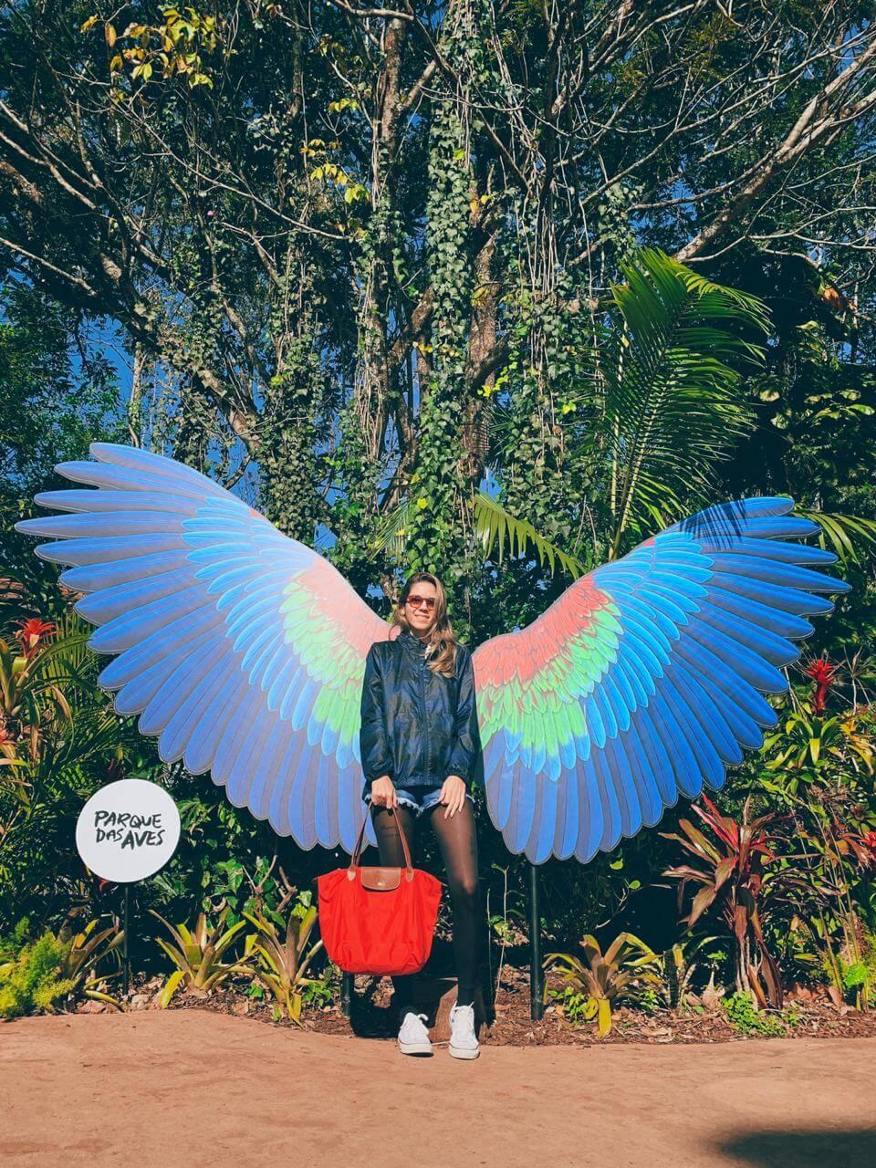 Manuela Brasão posa com asas de arara da decoração do Parque das Aves em Foz do Iguaçu.