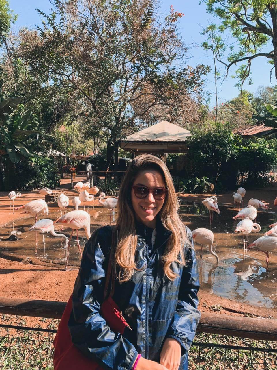 Manuela Brasão sorri no Parque das Aves em Foz do Iguaçu com flamingos do parque ao fundo.