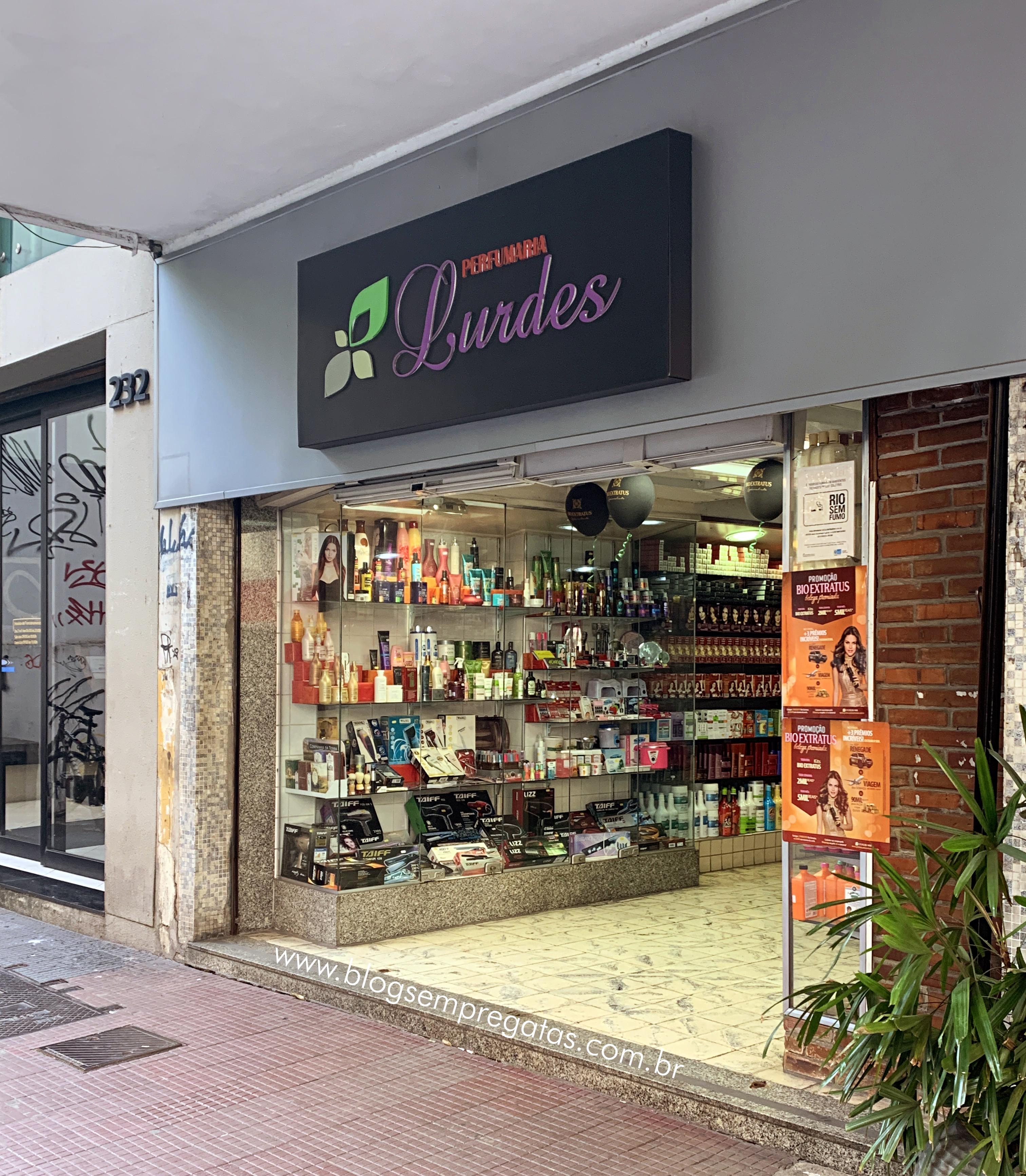 Entrada da Perfumaria Lurdes com letreiro com nome da marca e vitrine de produtos.