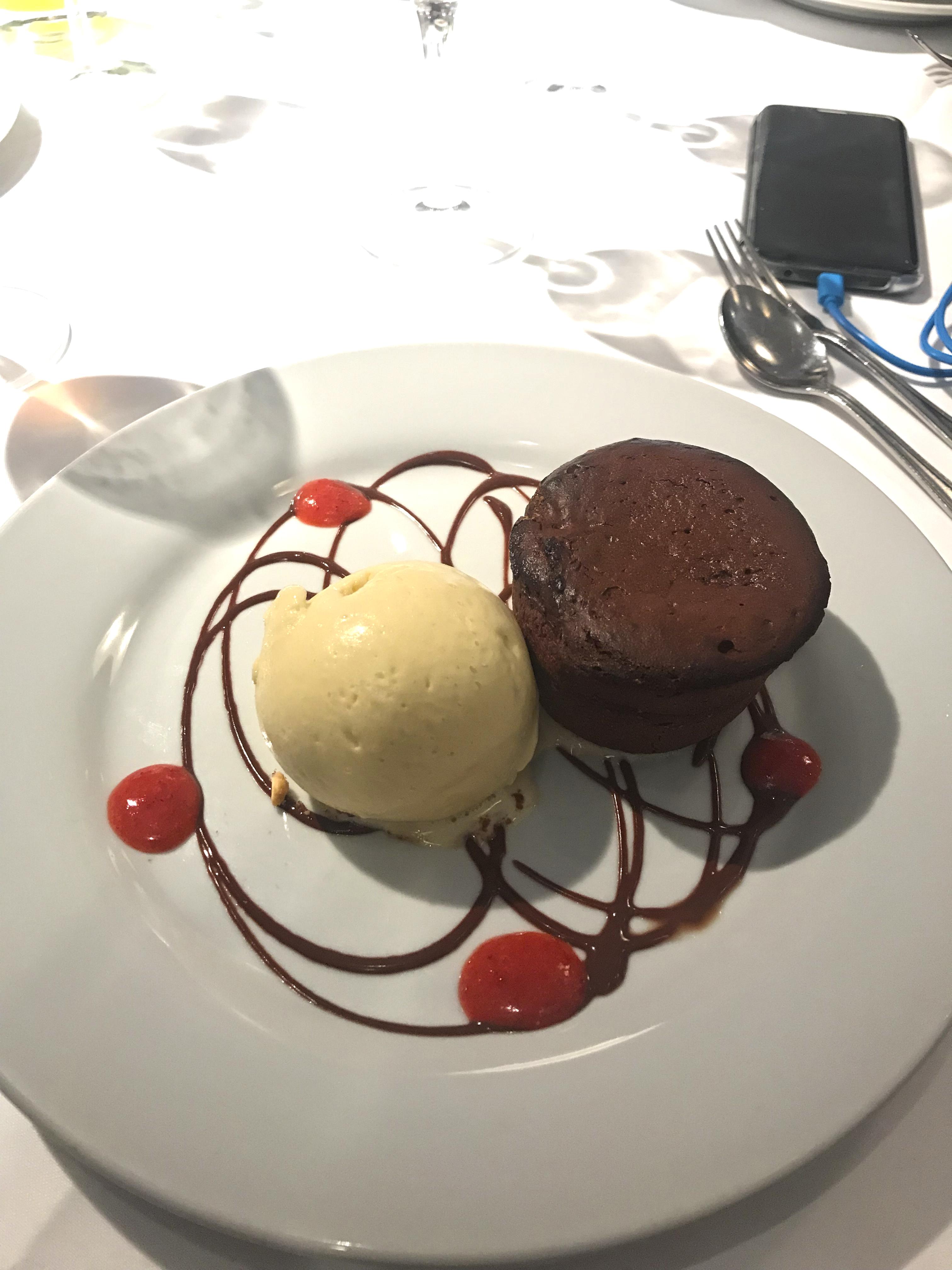Bolo de chocolate com sorvete de creme e decorações no prato feitas com calda de chocolate.