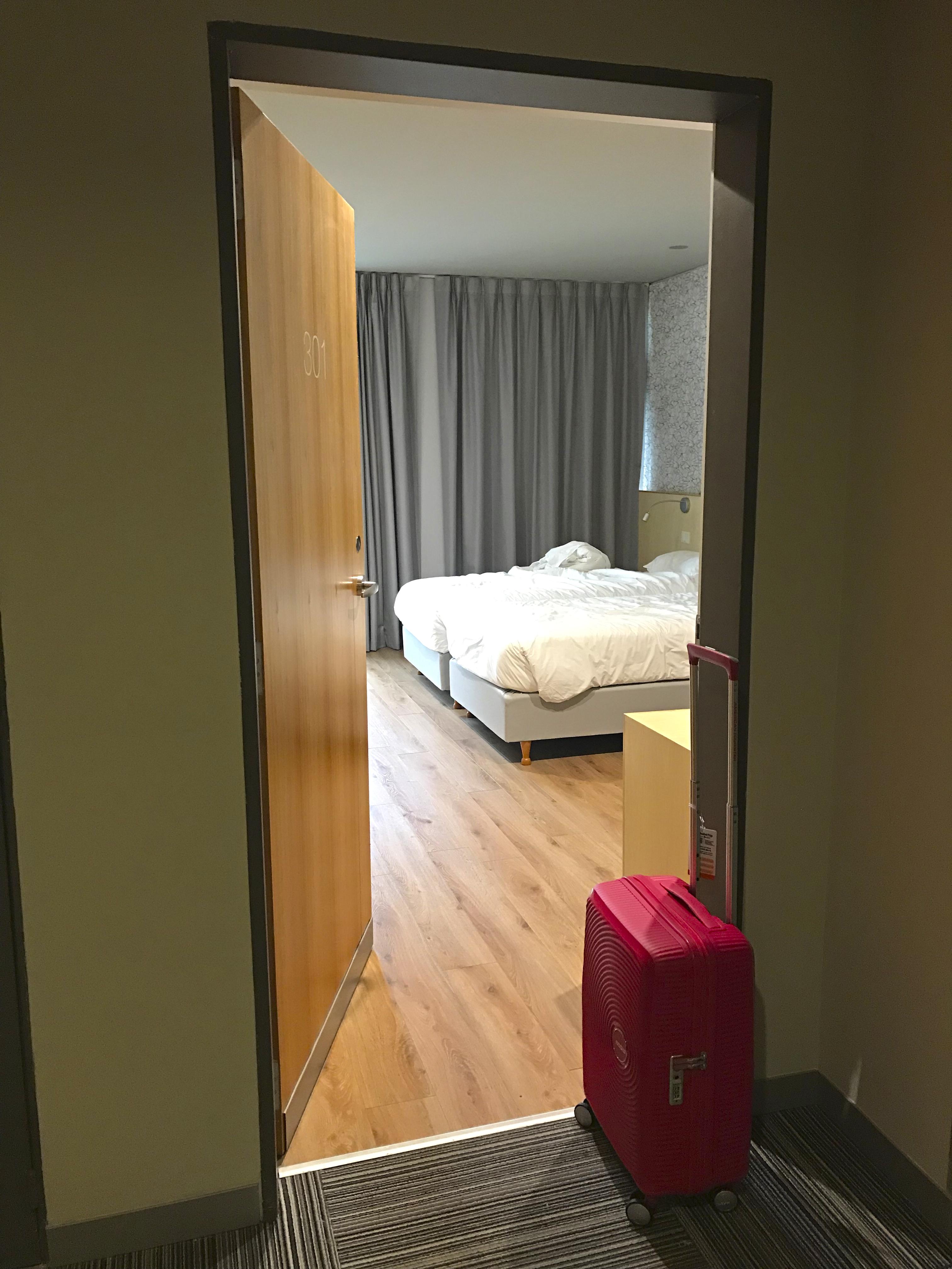 Entrada do quarto de hotel do Own Madero Buenos Aires com duas camas, bancada e cortinas ao fundo.