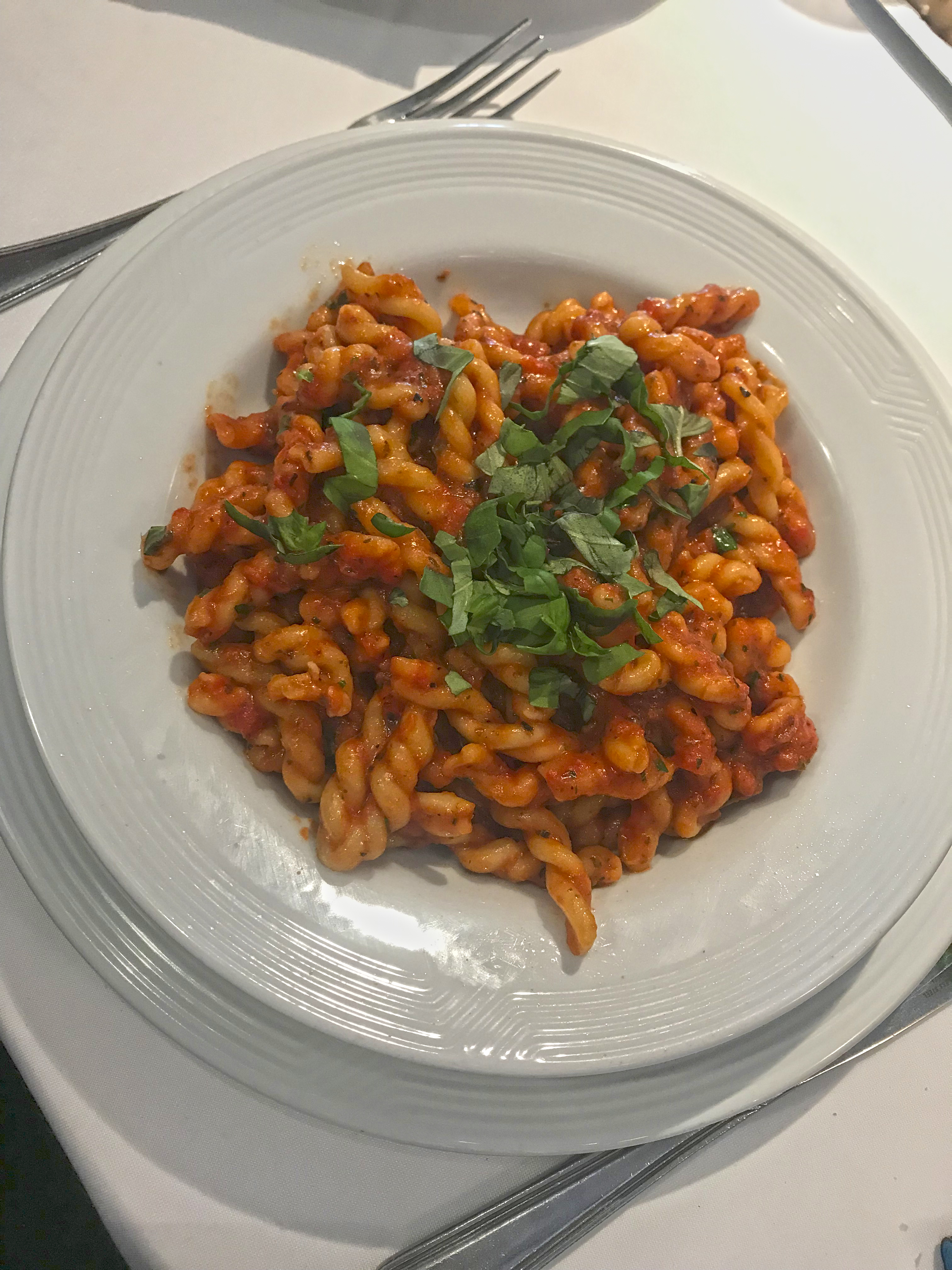Mesa com prato de tagliolini com molho de tomate e folhas de manjericão.