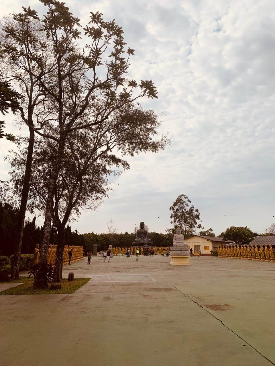 Pátio interno do templo budista de Foz do Iguaçu com pessoas andando, casinhas, estátuas e árvores.