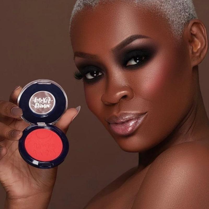 Modelo com blush coral intenso avermelhado.