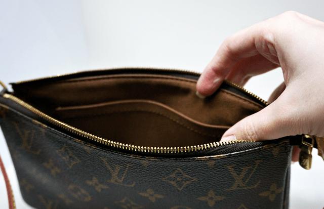 Interior da Pochette Accessoires Monogram da Louis Vuitton, forrado em tecido marrom escuro com um bolso sem fechamento.