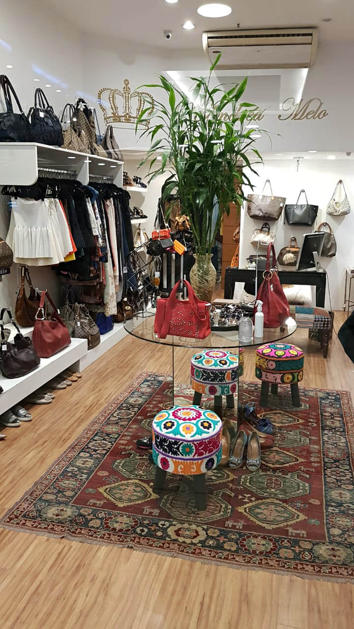 Interior do brechó de luxo Andrea Melo com roupas, sapatos e bolsas.