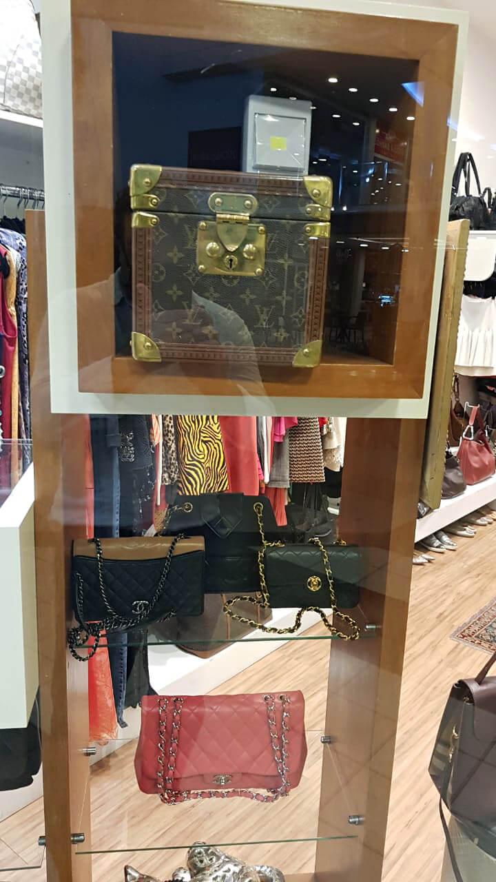 Vitrine com baú Louis Vuitton e bolsas Chanel.