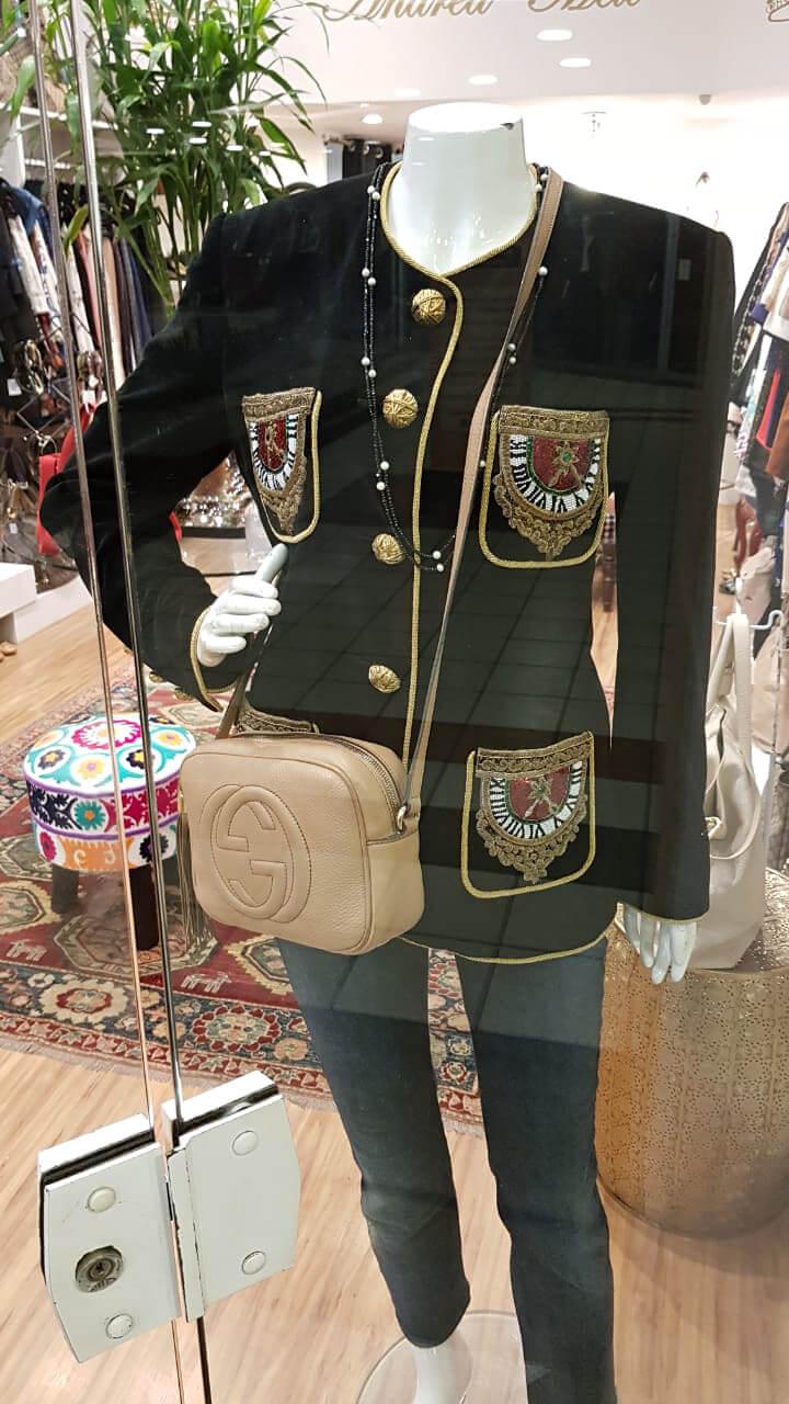 Vitrine com manequim vestindo blazer Dolce & Gabanna e bolsa Soho Disco da Gucci.
